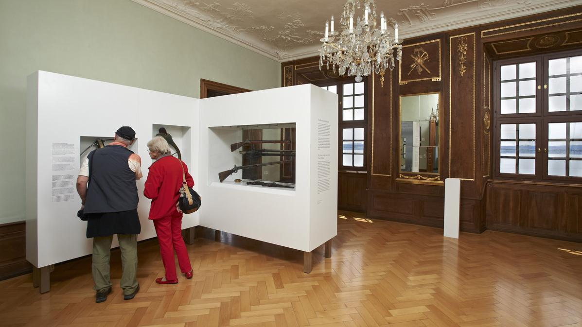 Besucher an Vitrine im Jagdzimmer, Neues Schloss Meersburg; Foto: Staatliche Schlösser und Gärten Baden-Württemberg, Arnim Weischer